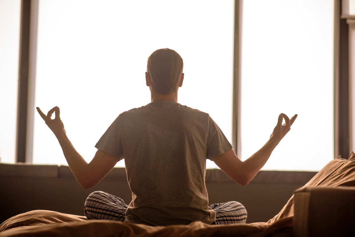 Man Meditating on Bed Facing Open Window